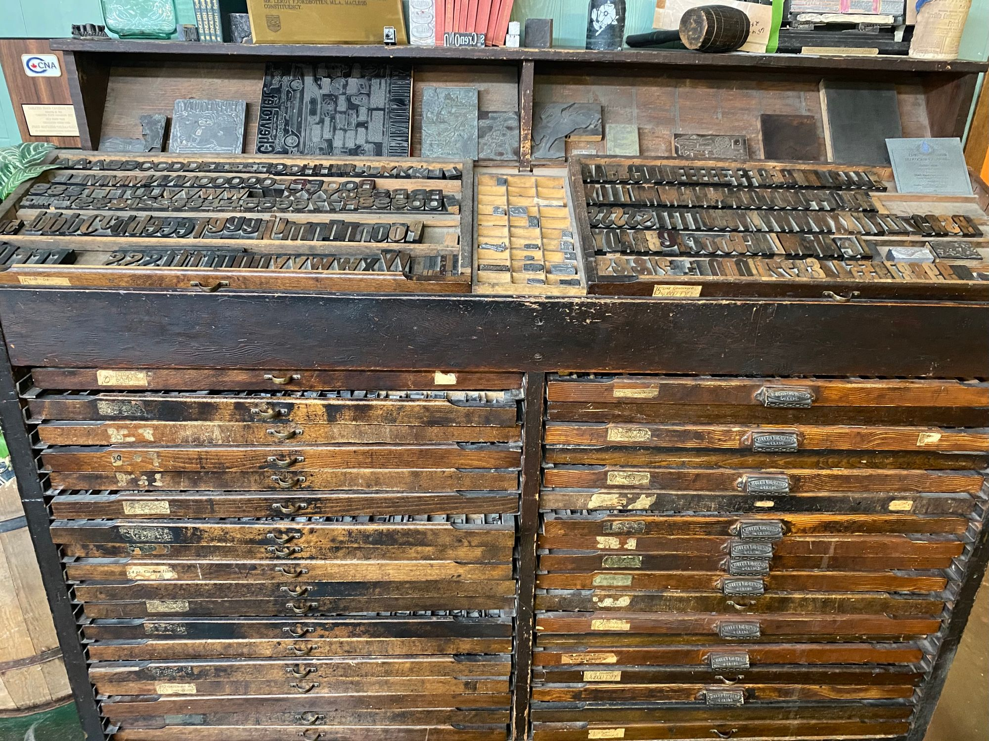Image: A newspaper printing cabinet that contains metal letters for a printing press.